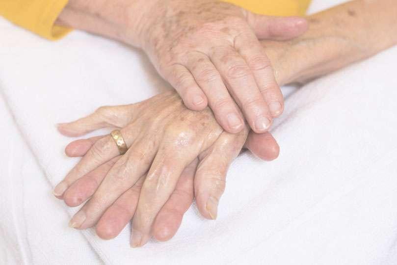 Judy massaging elderly lady's hand